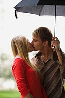 Teenage couple kissing under an umbrella (thumbnail)