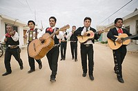 Mariachi band walking and playing their instruments