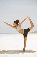Young woman stretching on the beach