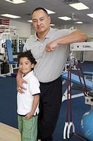 Physical trainer posing for the camera with his son in a gym