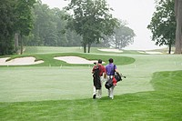 Rear view of two men walking on golf course