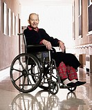 Elderly man smiling for the camera in a wheelchair