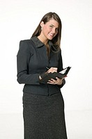 Businesswoman standing, writing in diary, posing