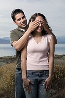 Young man covering young woman eyes, outdoors