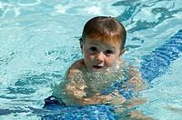 Boy (4-5), holding lane rope in swimming pool, portrait
