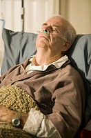 Senior man lying in bed in retirement home with tubes in nose