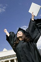 Young woman in graduation gown holding diploma in hand, cheering, low angle view