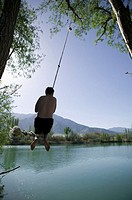 Man swinging on rope over water