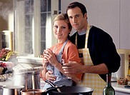 Couple in kitchen wearing aprons, portrait