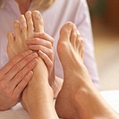 Woman getting foot massage by reflexologist (focus on hands and feet)