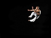 Man performing capoeira, jumping in midair