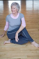 Senior woman stretching on hardwood floor, smiling