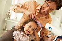 Father using hair dryer on daughter (2-4), smiling