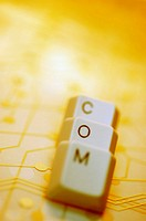 Close-up of computer keys on a circuit board spelling the word com