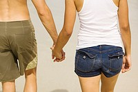 Mid section view of a young man and a teenage girl holding hands (thumbnail)