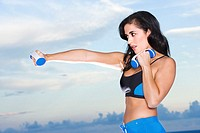Side profile of a mid adult woman exercising with dumbbells
