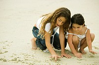 Two sisters playing with sand on the beach