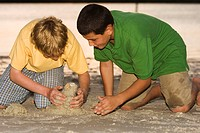 Close-up of two brothers playing in sand