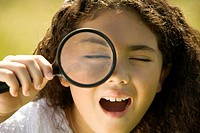 Close-up of a girl looking through a magnifying glass
