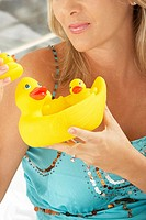 Close-up of a mid adult woman holding rubber ducks