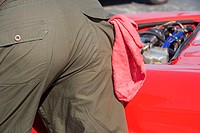 Mid section view of a mechanic near a car