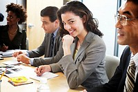 Businessmen and women in meeting, portrait of woman smiling