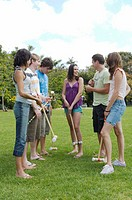 Young men and women standing in park with croquet set