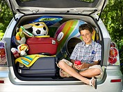 Boy (11-13) sitting in boot of car amongst luggage, portrait