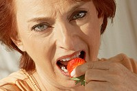 Portrait of a senior woman eating a strawberry