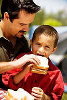 Close-up of a father feeding his son a sandwich