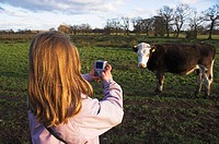 Girl child taking photo of cow with digital camera