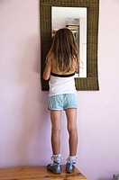 Girl child in running shorts with mirror