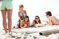 Young woman standing by group of friends lying on beach