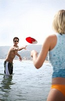 Young couple on beach, man throwing flying disc to woman, smiling