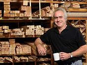 Man by planks of wood on shelves holding mug, smiling, portrait