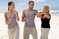 Senior woman teaching young woman and young man tai chi on beach