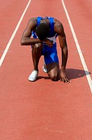 A Tired Male Runner Slumped Over on a Track