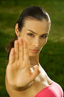 Portrait of a mid adult woman showing a stop gesture