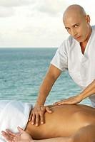 Portrait of a mature man giving a man a back massage