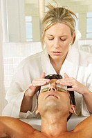 Massage therapist putting teabags on a young man´s eyes