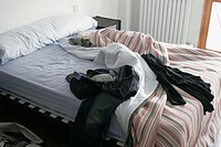 Unmade bed with clothes all over