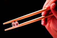 Hand picking up a dice with chopsticks