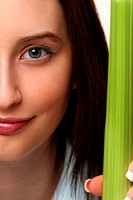 An up-close picture of a woman holding up a long green vegetable