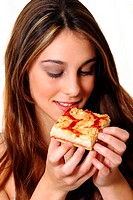 A woman looking at a piece of pizza she is holding