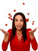 A woman in red blouse throwing tomatoes in the air