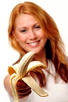 A woman in white shirt offering a peeled banana to the camera