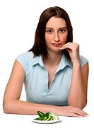 A woman in blue shirt posing with a plate of sliced cucumbers on the table