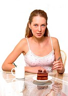 A woman holding a fork with a plate of chocolate cake and a cup of water on the table