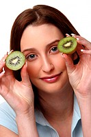 A woman holding up two halves of kiwi fruit