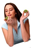 A woman holding up two halves of kiwi fruit but only looking at one